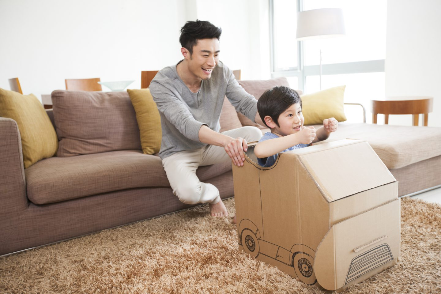 Father and son playing carton car in living room - FWD Car Insurance Singapore