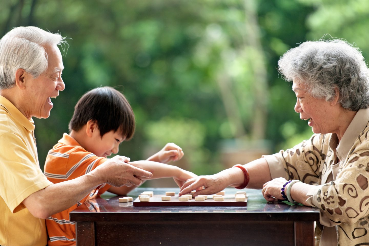 Grandfather, grandmother teaching grandson how to play Xiangqi (chinese chess) - FWD Insurance Singapore