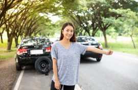 women after a car breakdown with Red triangle of a car on the road - FWD Car Insurance