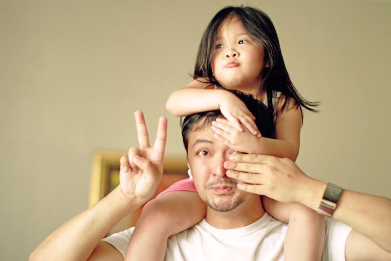 Small cute and chubby girl getting shoulder back ride while making faces. She is also covering eye of his uncle. FWD Cancer Insurance